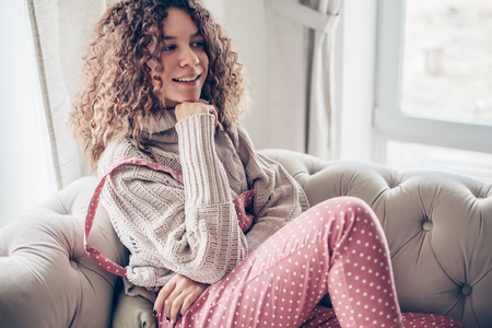 Hipster teenage girl with curly hair wearing beige knitted sweater and pink polka dot jumpsuit relaxing on a couch indoor