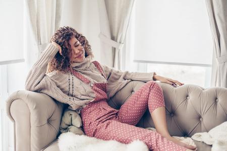 Hipster adolescente con pelo rizado vistiendo suéter de punto beige y mono de lunares rosa relajándose en un sofá interior
