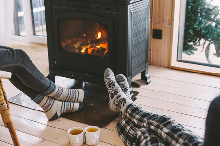 Cold fall or winter day. People drinking tea and resting by the stove. Closeup photo of human feet in warm woolen socks over fire place. Hygge concept of cozy winter weekend in cabin. Archivio Fotografico