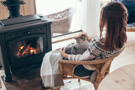 Human with cat relaxing in wicker armchair by the fire place in wooden cabin. Warm and cozy winter holiday concept. Stockfoto