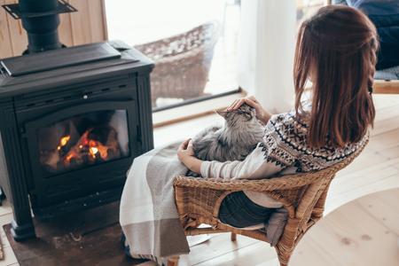 Humanos con gato relajante en sillón de mimbre junto a la chimenea en cabaña de madera. Concepto de vacaciones de invierno cálido y acogedor.