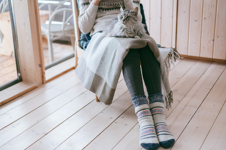 Young girl in sweater with cat relaxing on chair in log cabin near big window Imagens