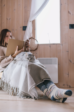 Young girl in sweater and warm socks relaxing on chair with cat and reading book in log cabin near window