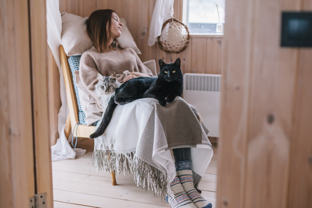 Young girl in sweater with cat sleeping on chair in log cabin near window