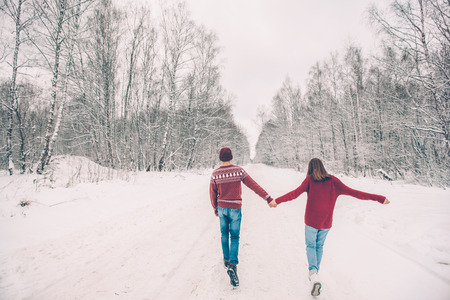 Photo of teenage friends in red Christmas sweaters walking in snow one winter day. People having good time on the January weekends.