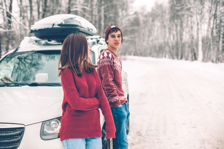Photo of teenage friends in red Christmas sweaters walking in snow one winter day. People having road trip on the January weekends. Stock Photo