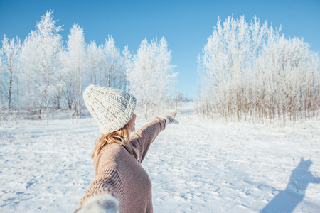 Photo of woman in sweater, gloves and knitted hat standing and looking at snowy forest in magic winter day. Follow me concept.