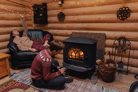 Teenage friends relaxing by the fireplace inside wooden cabin. Warm and cozy winter holiday indoor concept.