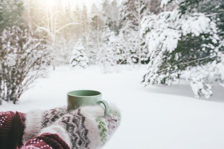 POV-Foto einer Tasse mit heißem Tee in menschlicher Hand in Handschuhen über verschneitem Wald an einem Wintermorgen