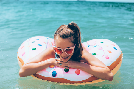 Tween girl relaxing on the inflatable ring on the beach in summer vacations