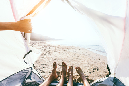 POV photo of young couple relaxing in a tent on the beach near the sea in summer. Sitting inside and viewing morning sunrise.