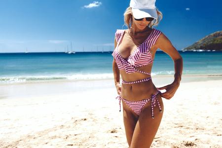 Il corpo della bella donna in bikini alla moda su sfondo spiaggia. Modello snello e abbronzato in posa sull'isola. Archivio Fotografico