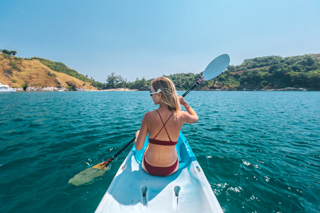 Woman paddling a kayak by the tropical beach. Kayaking tour in Phuket, Thailand Фото со стока - 116757779