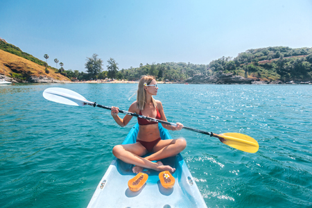 Woman paddling a kayak by the tropical beach. Kayaking tour in Phuket, Thailand Фото со стока - 116757781