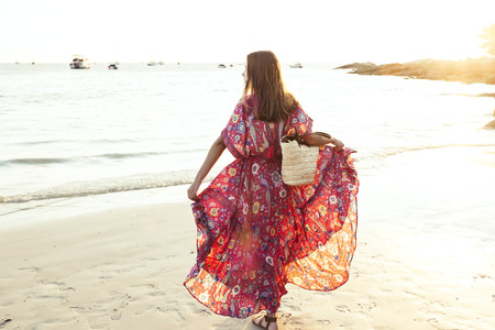 Young beautiful girl wearing boho maxi dress walking on sand. Summer fashion clothes for the beach. Stock fotó - 116758056