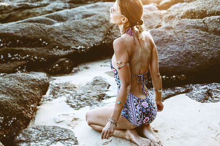 Photo of beautiful boho styled model wearing ethnic swimwear and silver bohemian jewelery on the beach in sunset