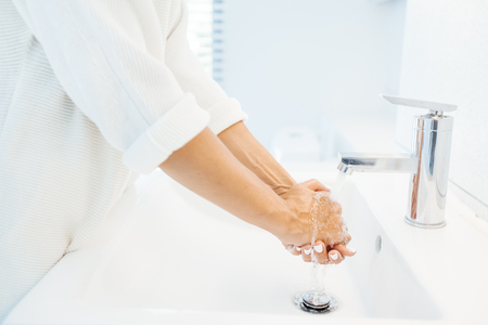 Closeup photo of person washing hands in white clean basin in home washroom Imagens