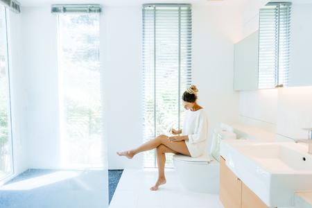 Foto einer Frau, die nach dem Duschen in einem luxuriösen Badezimmer Körperlotion auf ihre Beine aufträgt Standard-Bild