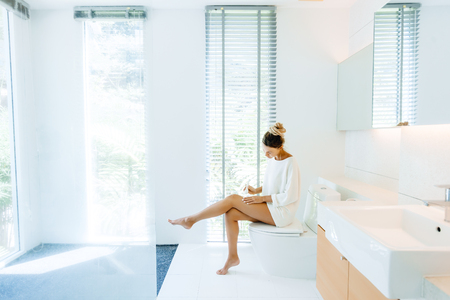Photo of woman applying body lotion to her legs after shower in luxury bathroom Stock Photo