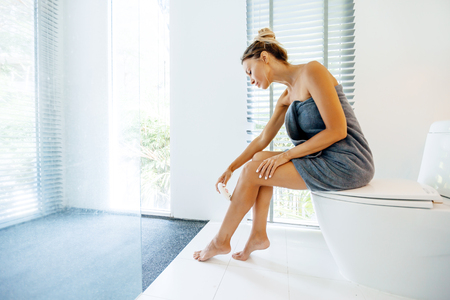 Photo of woman making hair removal on legs with electric epilator. Home depilation after shower in luxury bathroom.