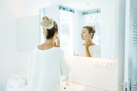 Photo of woman looking at mirror and applying face cream. Everyday morning routine in bathroom.