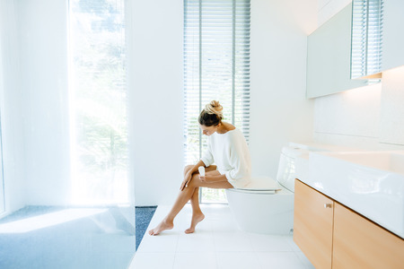 Photo of woman applying body lotion to her legs after shower in luxury bathroom Stok Fotoğraf