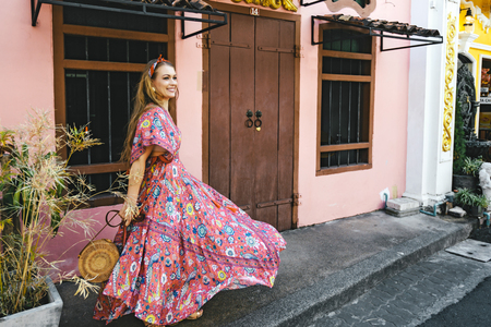 Boho girl in maxi dress and straw hat walking on the Asia city street. Travelling in Phuket Old Town in Thailand. Stok Fotoğraf