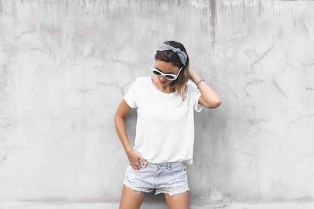 Hipster-Mädchen mit leerem weißem T-Shirt und Denim-Shorts posiert gegen graue Straßenmauer, leeres Modell für T-Shirt-Druckladen
