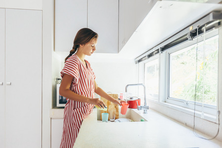 Teenage girl washing dish in the modern white kitchen. 12 years old girl doing housework. Stock Photo