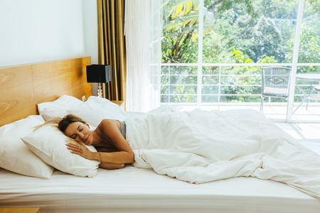 Woman sleeping on bed in luxury hotel room in the morning infront of big window. Chilling well on comfy matress and pillows. Stock Photo