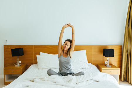 Woman waking up and stretching on bed in luxury hotel room in the morning. Sleeping well on comfy matress and pillows. Good starting of the day. 스톡 콘텐츠