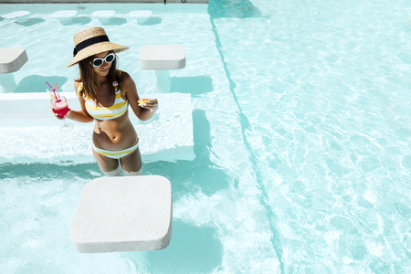 Girl relaxing and drinking watermelon cocktail in the hotel pool. Healthy fruit summer diet. Tropical beach lifestyle.
