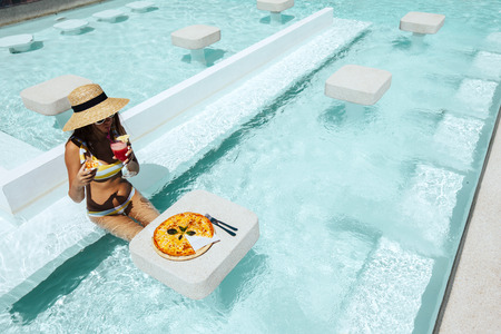 Girl relaxing and eating pizza and drinking cocktail in the hotel pool. Luxury tropical beach lifestyle.