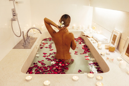 Woman relaxing in luxury bath decorated with candles and flower petals. Organic skin care in tropical spa resort.