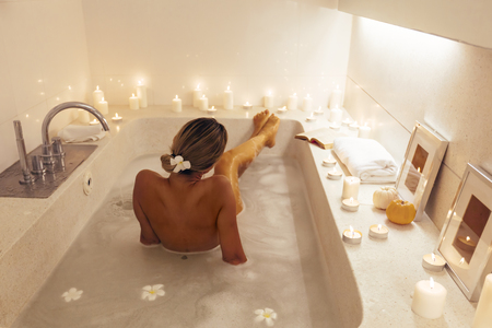 Woman relaxing in luxury spa bath decorated with candles. Spending romantic evening or night in bathroom.