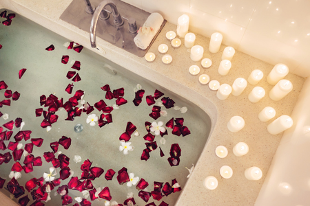 Prepared luxury spa bath decorated with flower petals and candles, top view from above. Фото со стока - 117110151