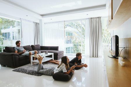 Two teenagers watching tv while relaxing on couch in living room