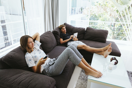Two teenagers using ipad and watching tv while relaxing on couch in living room 版權商用圖片 - 117110629