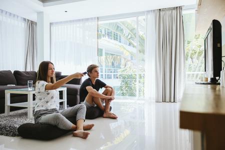 Twee tieners die tv kijken terwijl ze ontspannen op de bank in de woonkamer Stockfoto