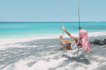Back view of girl with pink hear having fun on swing hanging on tree at tropical beach with white sand. Luxury vacation on paradise island. Stock Photo