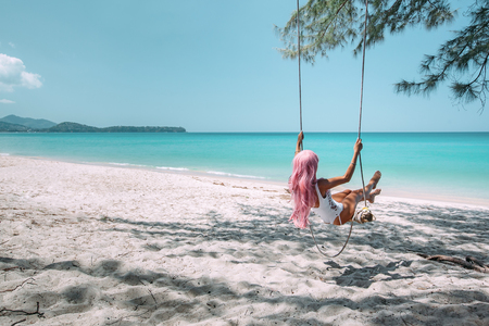 Back view of girl with pink hear having fun on swing hanging on tree at tropical beach with white sand. Luxury vacation on paradise island. Imagens