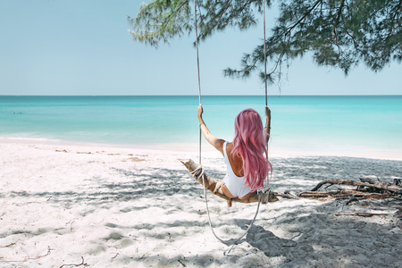 Back view of girl with pink hear having fun on swing hanging on tree at tropical beach with white sand. Luxury vacation on paradise island. Stockfoto
