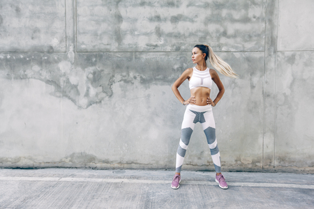 Fitness model in sportswear posing on the city street over gray concrete background. Outdoor sports clothing and shoes, urban style.