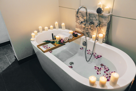 Prepared luxury spa bath decorated with flowers and candles, with wooden tray on it Stock Photo