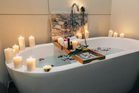 Bañera de hidromasaje de lujo preparada decorada con flores y velas, con bandeja de madera sobre ella