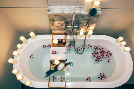 Prepared luxury spa bath decorated with flowers and candles, with wooden tray on it, top view from above Фото со стока