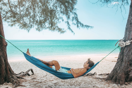 Teenage boy chilling in hammock under the shade of a tree on tropical beach , hot sunny day Banque d'images