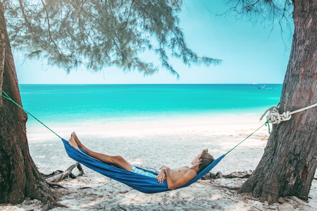 Teenage boy chilling in hammock under the shade of a tree on tropical beach , hot sunny day Reklamní fotografie