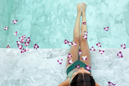 Girl relaxing in tropical spa pool decorated with flowers in luxury hotel. Banque d'images