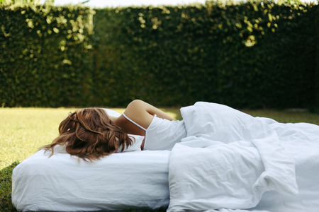 Teenage girl sleeping on soft mattress and pillow on grass outside. Healthy relaxing on cosy bed on fresh air in garden. 写真素材 - 118569204